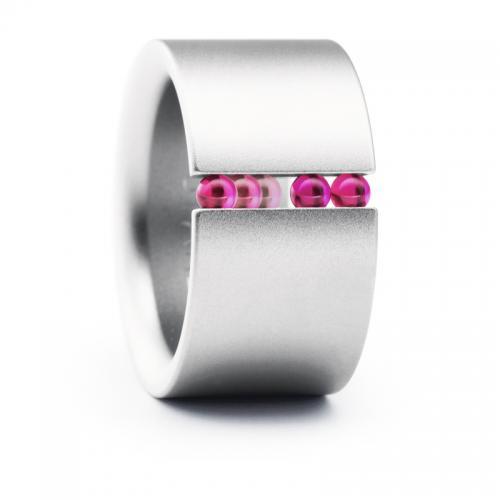 Der Abakus Ring von Niessing, breiter Stahl und kräftige, rote Kugeln